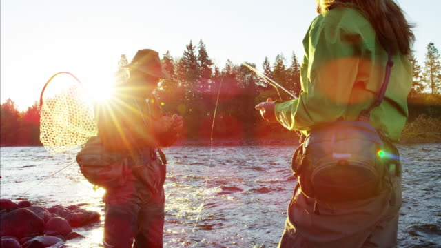 stockvideo's en b-roll-footage met skilled male and female casting line freshwater fishing - vrouwtjesdier