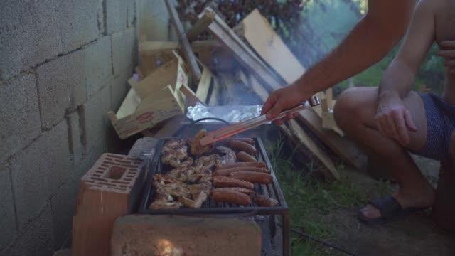 裏庭で喫煙バーベキューを準備する熟練した男性 - コイントス点の映像素材/bロール
