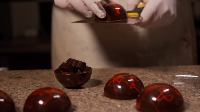 skilled pastry baker making decorated chocolate spheres - stuffed stock videos & royalty-free footage