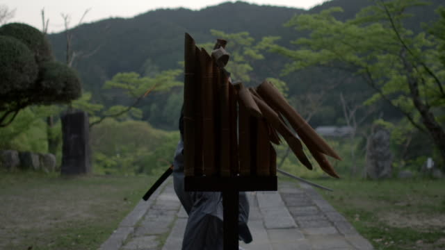 a skilled practitioner of kendo slices through bamboo - 武道点の映像素材/bロール