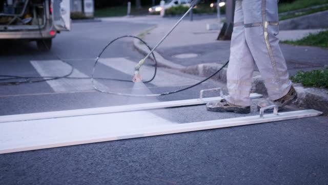 skilled road marking crew member spray painting crosswalk - freshly painted stock videos & royalty-free footage