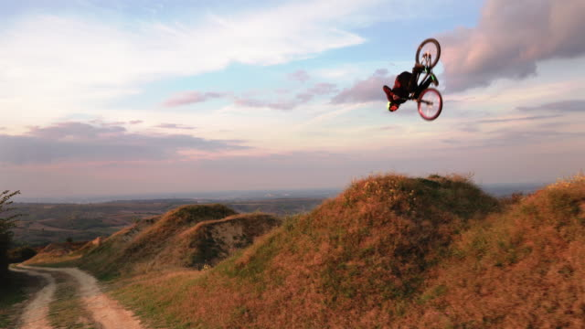 Skillful man on mountain bicycle practicing on extreme terrain.