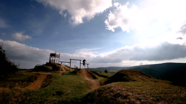 Skillful mountain bike cyclist jumping over dirt hills while exercising on extreme terrain.