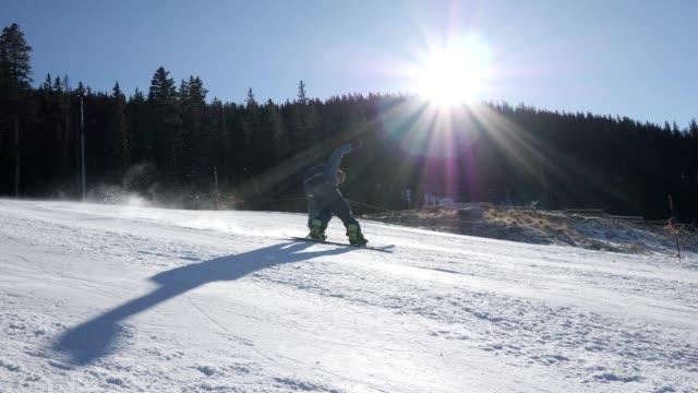 stockvideo's en b-roll-footage met behendig snowboarder springt als hij onder aan de heuvel nadert - colorado
