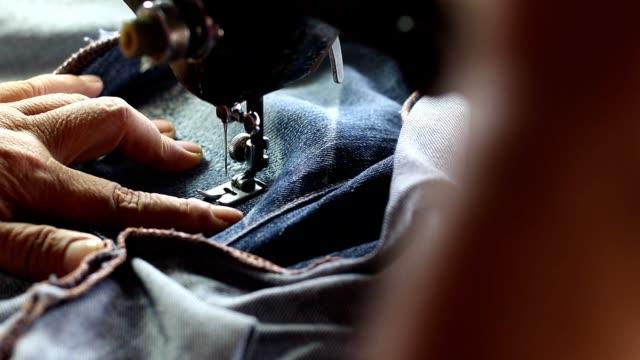 geschickt reparatur denim mit einer alten nähmaschine. - jeans stock-videos und b-roll-filmmaterial