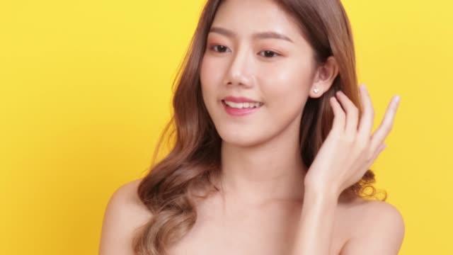 スキンケアコンセプト。黄色の背景スタジオ撮影でアジアの美しさの女性手のタッチ顔と肩をポーズ肖像画 - 絵画モデル点の映像素材/bロール