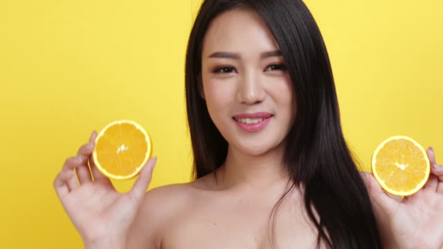 skin care concept. portrait posing asia beauty woman hand touch face and shoulder with yellow background studio shooting.asia female smile happyness holding fresh orange slide - ascorbic acid stock videos & royalty-free footage