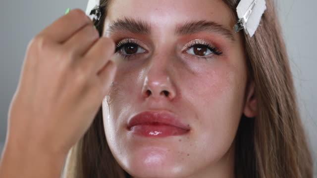 彼女の顧客の顔に油を置くスキンケアの専門家 - 美容専門家点の映像素材/bロール