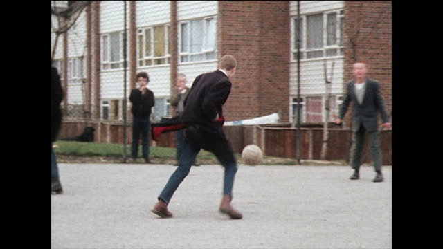 skinhead boys in black overcoats play football; 1980 - teenagers only stock videos & royalty-free footage