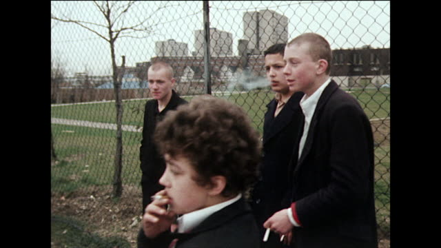 skinhead boys in black overcoats stand around smoking ; 1980 - teenagers only stock videos & royalty-free footage