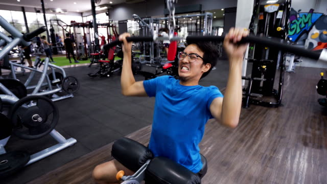 stockvideo's en b-roll-footage met skinny man proberen hard en falen in de sportschool, wide-grip lat pulldown - krachttraining