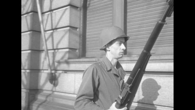 a skinny united states soldier with a bayoneted rifle walks back and forth of a large building with others at entrance - bajonett stock-videos und b-roll-filmmaterial