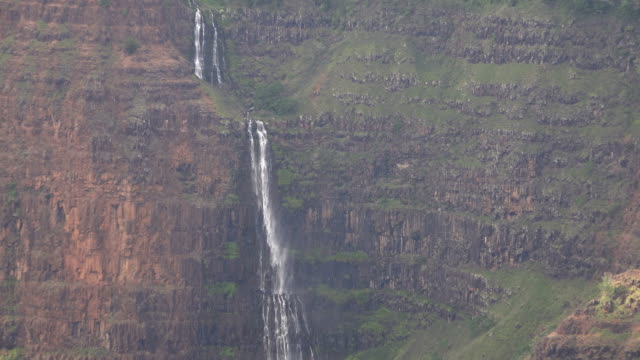 skinny waterfall on side of mountain on kauai island - butte rocky outcrop stock videos & royalty-free footage