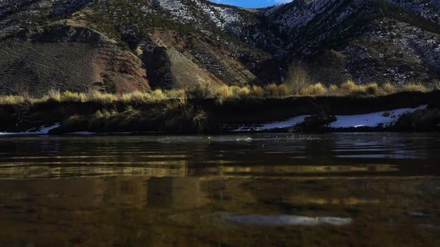 stockvideo's en b-roll-footage met overslaan van de rotsen langs de schilderachtige rivier - huppelen