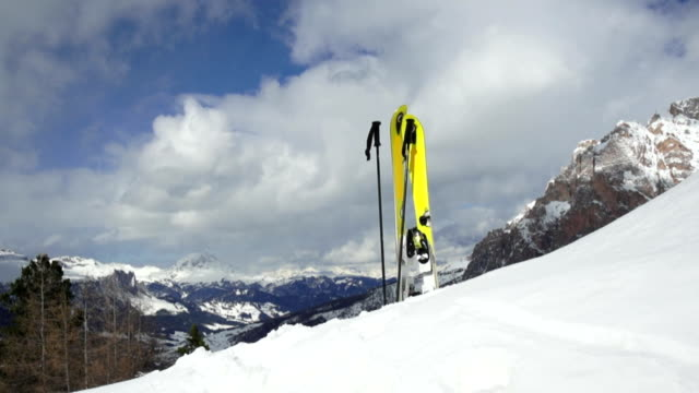 stockvideo's en b-roll-footage met pan skis standing iin snow on mountain top - geel