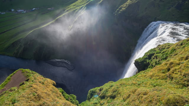 vidéos et rushes de cascade de skogafoss en islande, vue depuis le sentier touristique - mousse végétale