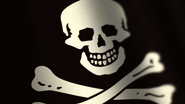 skull and cross bones pirate flag - loop. 4k. - skull stock videos and b-roll footage