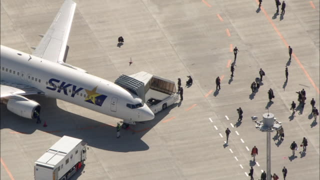 sky airlines passengers disembark from a plane at ibaraki airport on opening day as a service truck approaches the aircraft. - 降り立つ点の映像素材/bロール