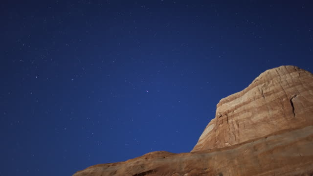 t/l ws sky and stars above rocky mountain, night to day / lake powell, utah, usa - rock formation stock videos & royalty-free footage