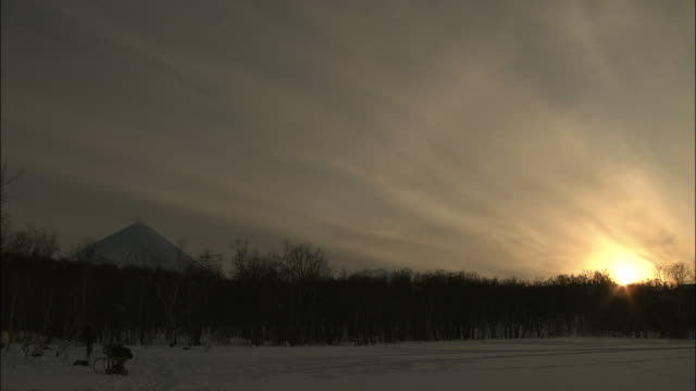 sky and sun in the evening  forest and klychevskaya sopka in silhouette - russia stock videos and b-roll footage