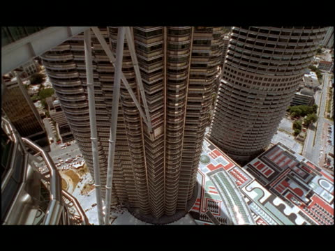 a sky bridge spans the gap between the famous petronas towers. - petronas twin towers stock-videos und b-roll-filmmaterial