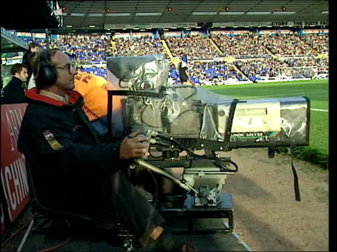 sky broadcast deal with football league ext cameraman filming football match commentators in commentary box during match - commentary box stock videos and b-roll footage
