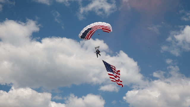 A sky diver flying the American flag lands in the middle of Yeagley Field during the 2016 Men's Little 500 at Indiana University The Little 500 is a...