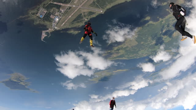 sky divers in free fall above city and green fields - quartet stock videos & royalty-free footage