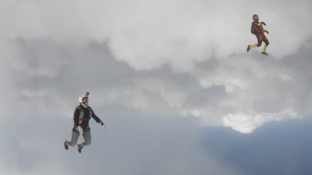 sky divers in free fall flying through clouds at high speed - skydiving stock videos & royalty-free footage
