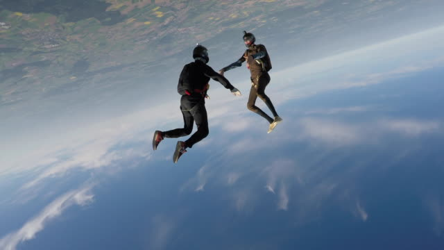 sky divers in free fall performing acrobatics - skydiving stock videos & royalty-free footage