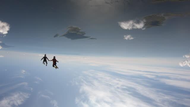 sky divers i fritt fall utför akrobatik - parachuting bildbanksvideor och videomaterial från bakom kulisserna