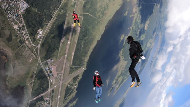 sky divers in free fall performing acrobatics - three people stock videos & royalty-free footage