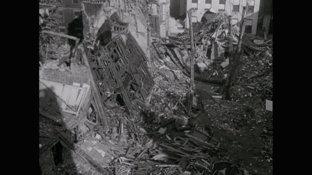WS POV TD PAN Sky fillled with barrage balloons, burning balloon, fighter plane smashes into ground with explosion, POV from fighter plane, shoots other plane which explodes, flies through explosion, soldier clearing bomb damage during London blitz