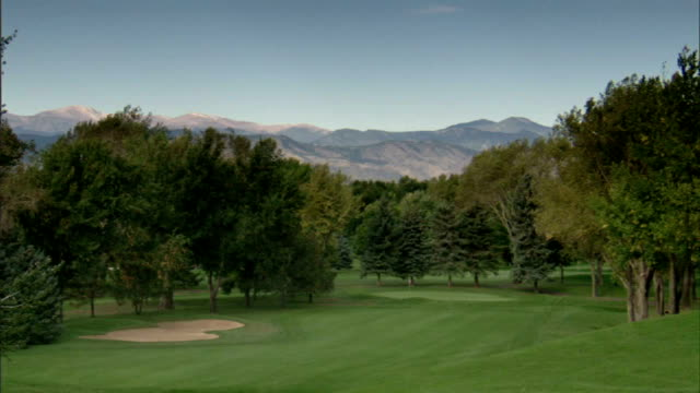 TU Sky TD WS First hole fairway sloping green lined w/ trees Rocky Mountains distant BG