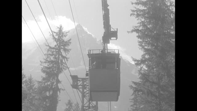 mls sky lift cable car proceeds out of shelter towards camera / mls car proceeds away from camera trees and clouds in background / pov from inside... - ski lift stock videos & royalty-free footage