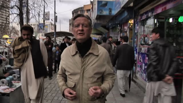 vídeos de stock, filmes e b-roll de sky news stuart ramsay reporting on elections held in afghanistan shows anon muslim women wearing a burka burkha burqa urdu bourkha burku walking on... - véu