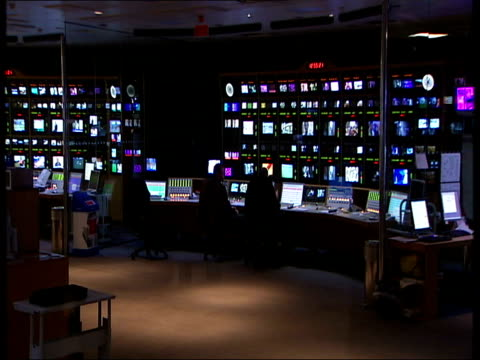 london int sky television control room or gallery with television monitors showing different channels and people working at desks including closeup... - television show stock videos & royalty-free footage