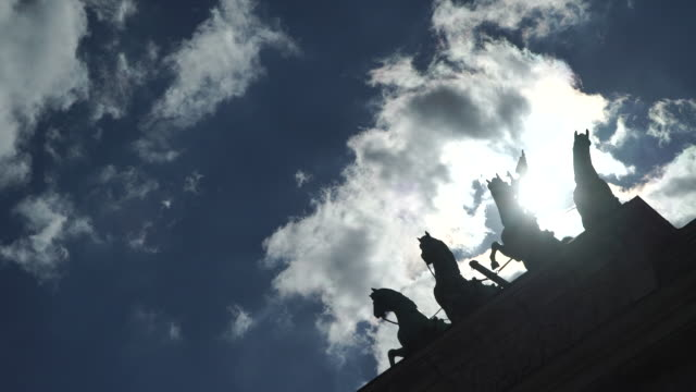 sky view over quadriga statue on brandenburg gate, berlin, germany - zugpferd stock-videos und b-roll-filmmaterial