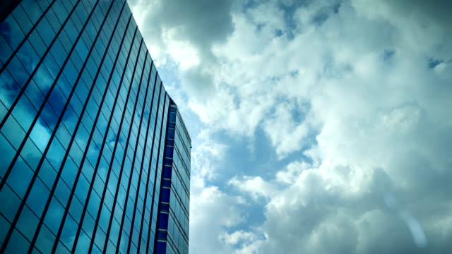 himmel mit beweglicher wolke reflektieren auf dem fensterglas des bürogebäudes - fensterfront stock-videos und b-roll-filmmaterial