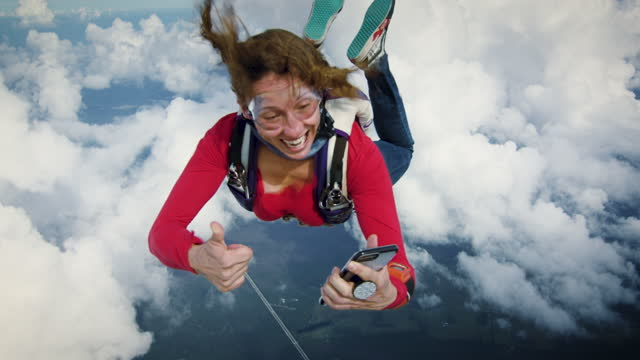 skydiver checking her smartphone - mid air stock videos & royalty-free footage