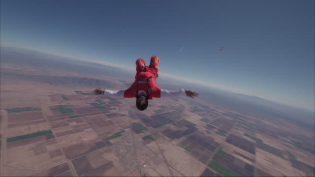 Skydiver exits plane and does a series of spins and acrobatics.