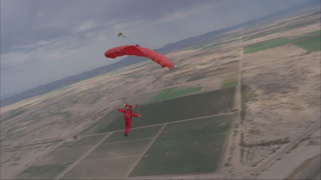 vídeos de stock, filmes e b-roll de a skydiver flies around under a red parachute. - membro humano
