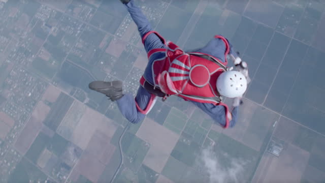 a skydiver frantically pulls on his parachute's ripcord while free falling. - free falling stock videos & royalty-free footage