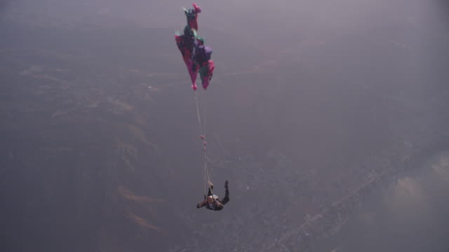 skydiver in business suit falls under a malfunctioning parachute - imbracatura di sicurezza video stock e b–roll