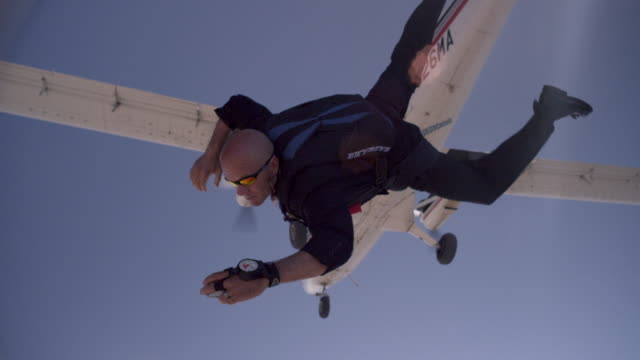 Skydiver in business suit with phone exits airplane