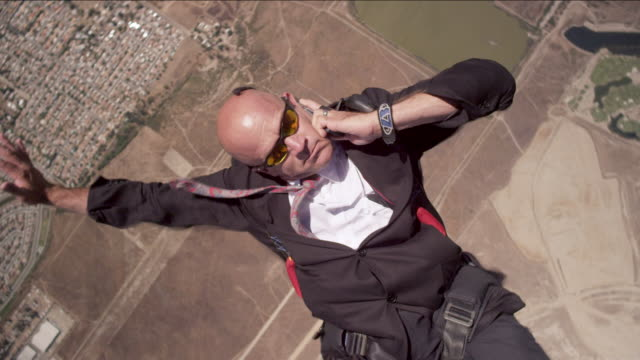 Skydiver in business suit with phone in free fall