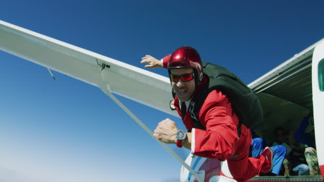 skydiver in red suit with wristwatch exits airplane - millennial generation stock videos & royalty-free footage