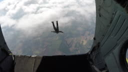 Skydiver jumping out of rear of airplane