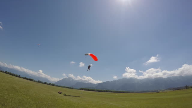 skydiver landing in field - parachuting stock videos & royalty-free footage