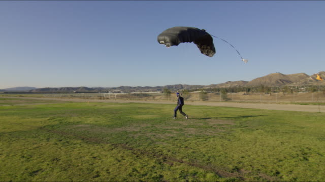skydiver lands his parachute on the grass - anticipation stock videos & royalty-free footage